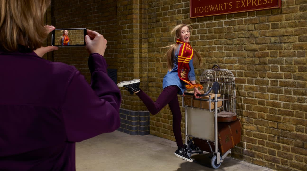 a girl pretending to enter Platform 9 3/4